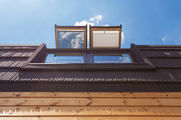 Open skylights (mansard windows) in wooden house with tile against blue sky